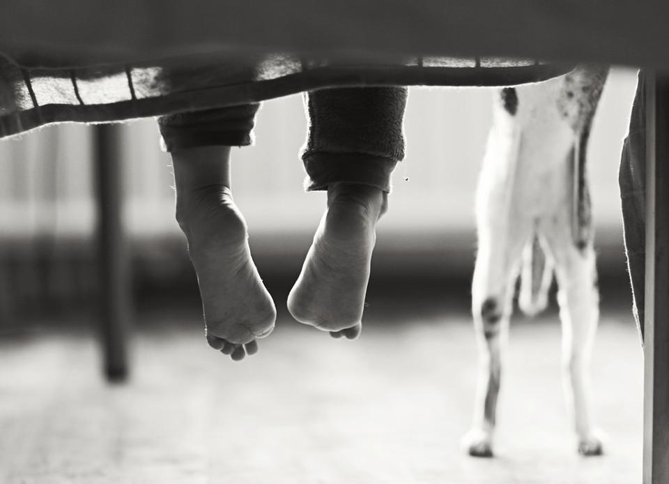 Schwarzweißfoto eines Tieres mit Kinderfüßen daneben.