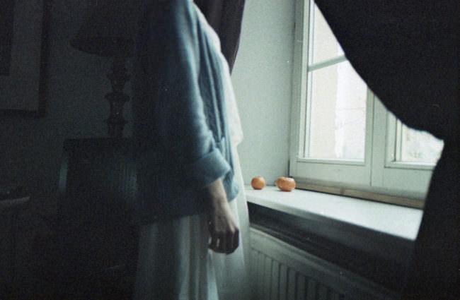 Eine Frau steht am Fenster, auf dem Fensterbrett liegen Orangen.