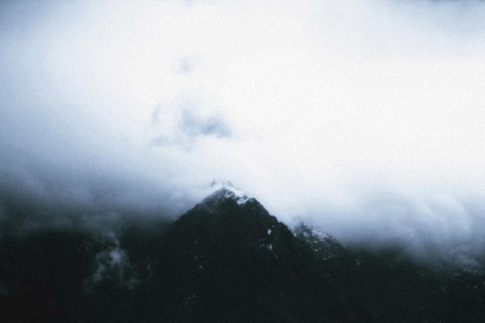 Wolkenformationen am Himmel über einem schwarzen Berg.