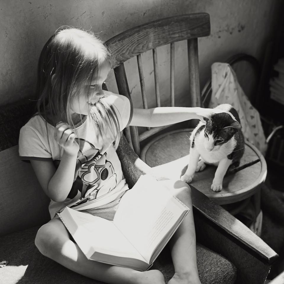 Schwarzweißfoto eines Mädchens beim Lesen mit einer Katze.