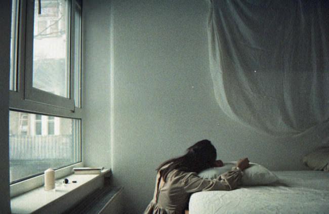 Eine Frau stützt sich auf ihr Bett.