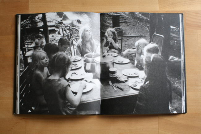 In einem Buch sitzen Kinden an einem Tisch und essen.