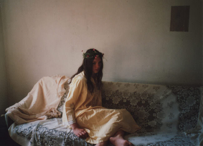 Eine Frau mit Blumenkranz sitzt auf dem Sofa.