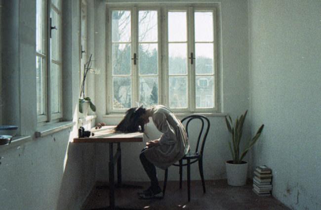 Eine Frau sitzt am Schreibtisch, den Kopf auf dem Tisch liegend.