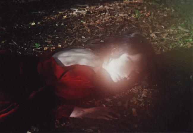 Eine Frau liegt auf dem Boden in einem roten Kleid.