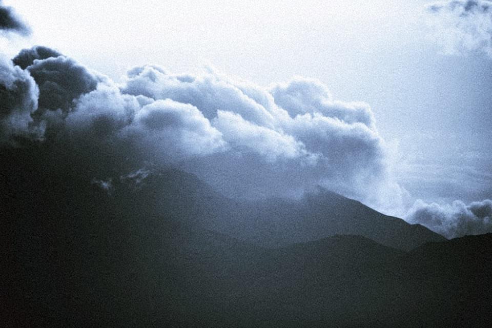 Weiße Wolkenformationen am Himmel über Bergen.