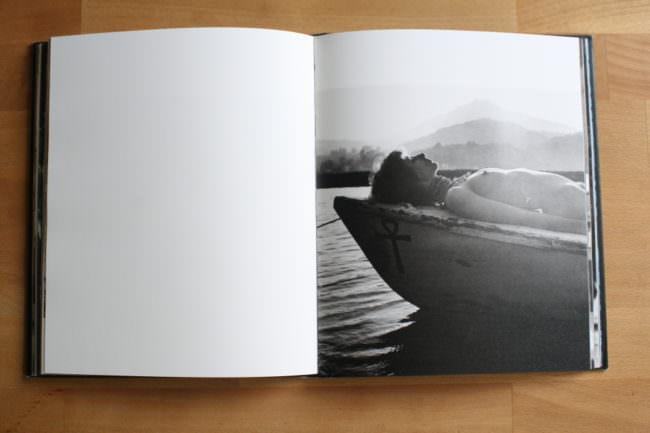 Eine Frau liegt nackt auf einem Boot mit Gebirge im Hintergrund.