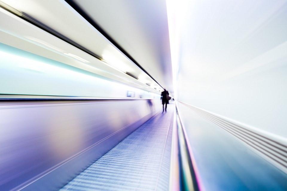 Eine Person in der Ferne auf einem Laufband in weiß und blau.