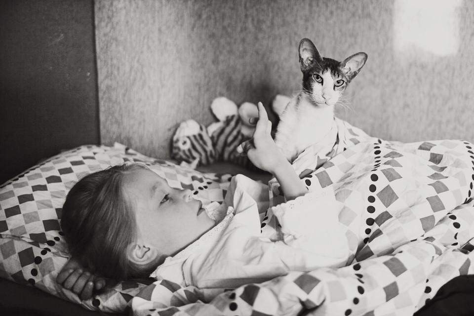 Schwarzweißfoto eines Mädchens im Bett mit einer Katze.