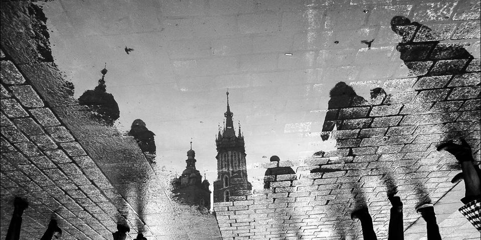 Schwarzweißaufnahme eines Architekturspiegelung in einer Pfütze.