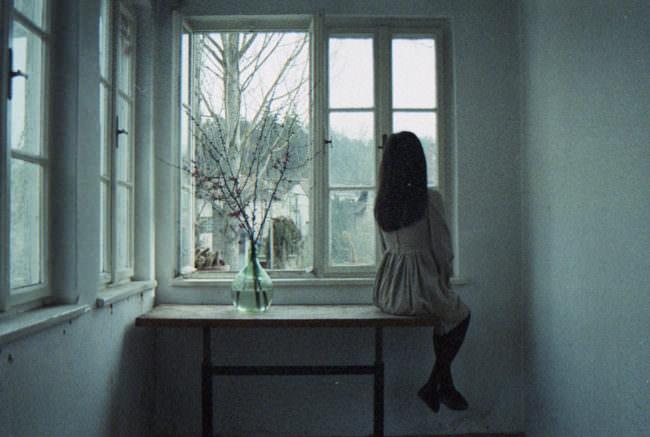Eine Frau sitzt auf dem Tisch und schaut aus dem Fenster.
