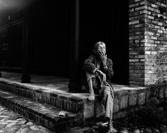 Ein alter Mann sitzt rauchend auf einer Steintreppe vor einem Gebäude.