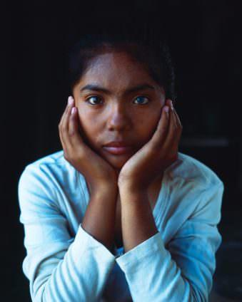 Nahes Portrait eines Mädchens, das ihren Kopf auf ihre Hände stütz.