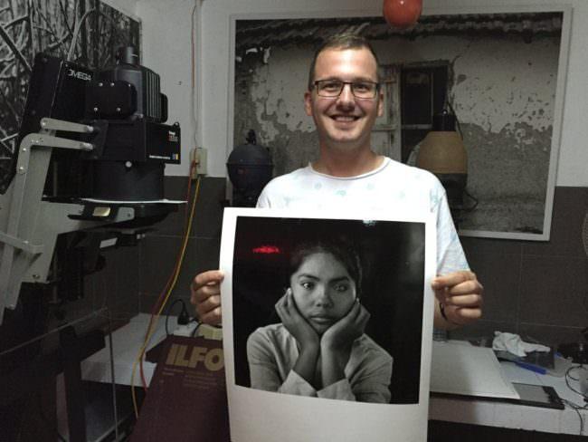 Ein Mann hält stolz einen großen Fotoabzug in die Kamera.