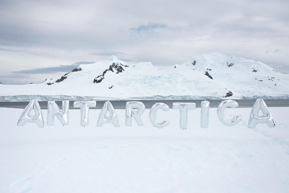 Silberne Luftballons mit den Buchstaben Antarctica vor Eisbergen.