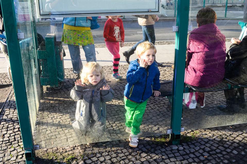 Zwei Kinder an einer Bushaltestelle