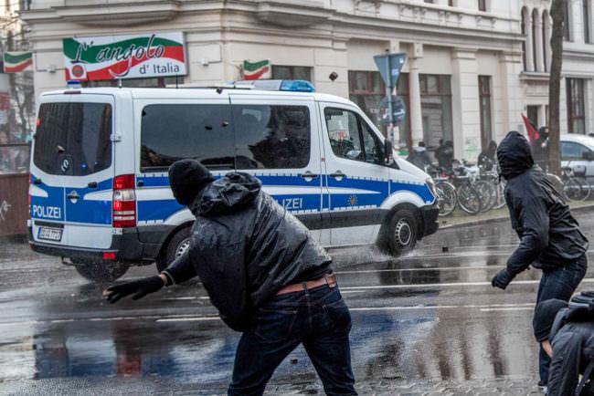 Eine Person bewirft ein Polizeiauto