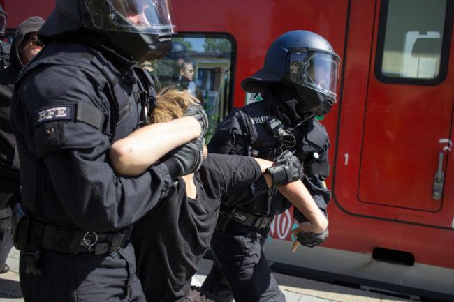 Polizisten führen eine Person ab