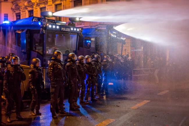 Polizisten stehen vor schießenden Wasserwerfern