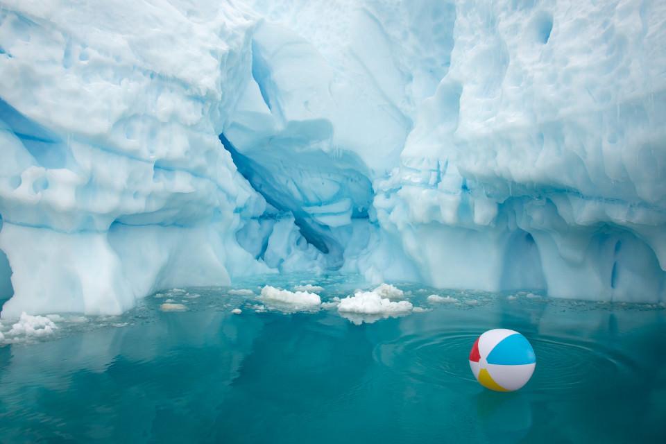 Ein bunter Wasserball vor einem Eisgletscher.
