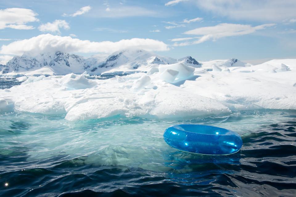 Ein blauer Schwimmreif treibt vor einer Eislandschaft.