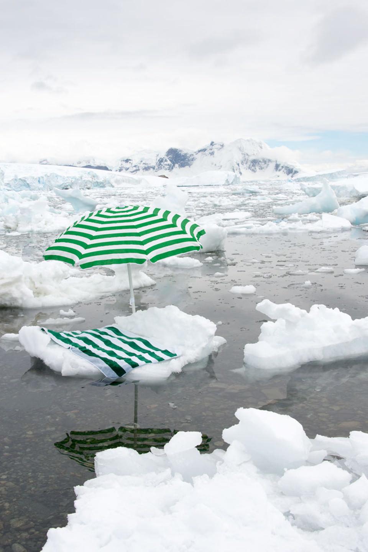 Ein grünweißer Sonnenschirm mit Badetuch liegen auf einer Eisscholle.