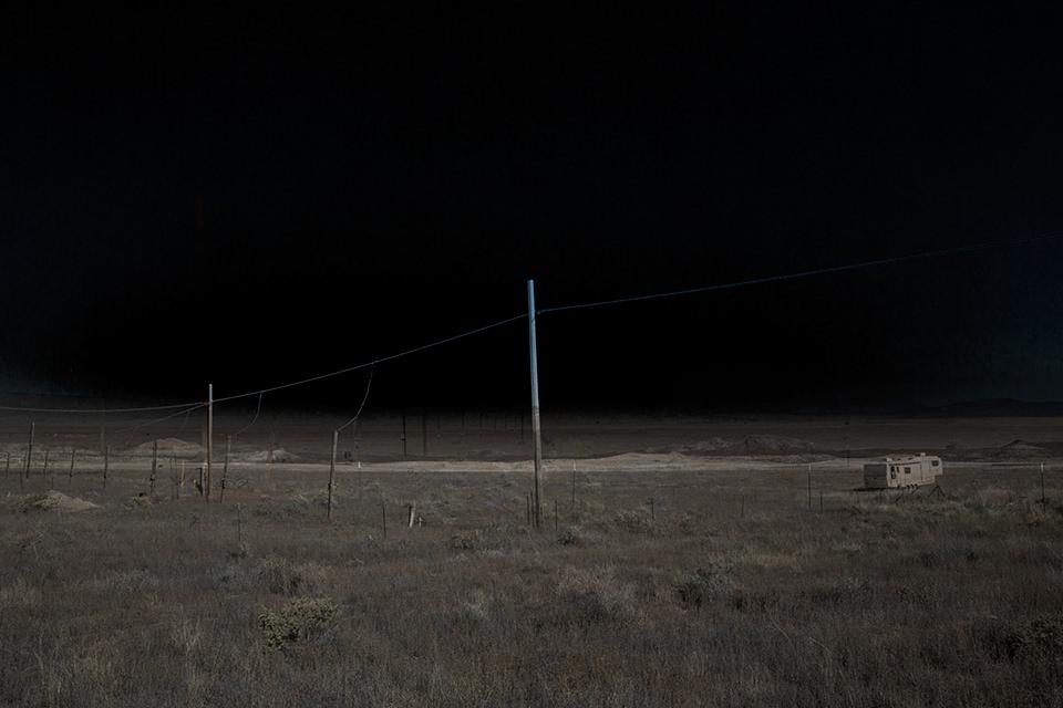 Eine ausgeleuchtete Wüstenlandschaft mit einer Stromleitung und Masten.