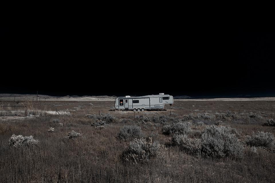 Eine ausgeleuchtete Wüstenlandschaft mit einem alten Camper vor Nachthimmel.