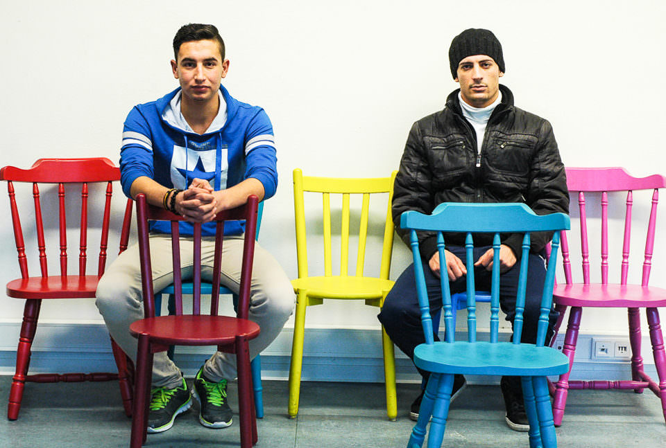 Zwei junge Männer sitzen auf bunten Stühlen