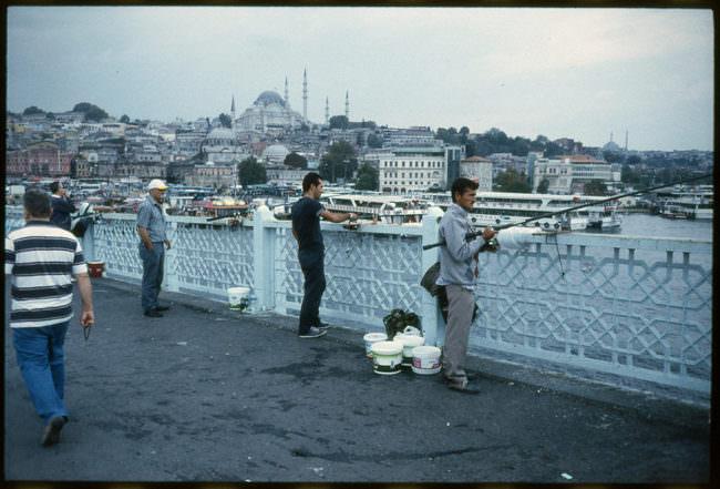 Fischer stehen auf einer Brücke mit ihren Angeln.