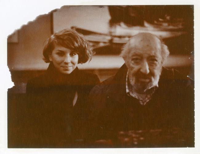 Eine junge Frau und ein älterer Mann schauen in die Kamera.