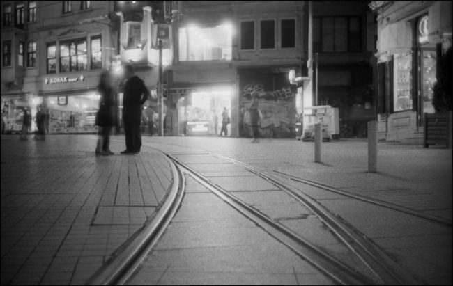 Straßenbahnschienen, Menschen, unscharf und Abendbeleuchtung.