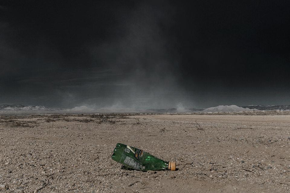 Eine ausgeleuchtete Wüstenlandschaft mit einer zerbrochenen Flasche im Verdergrund.