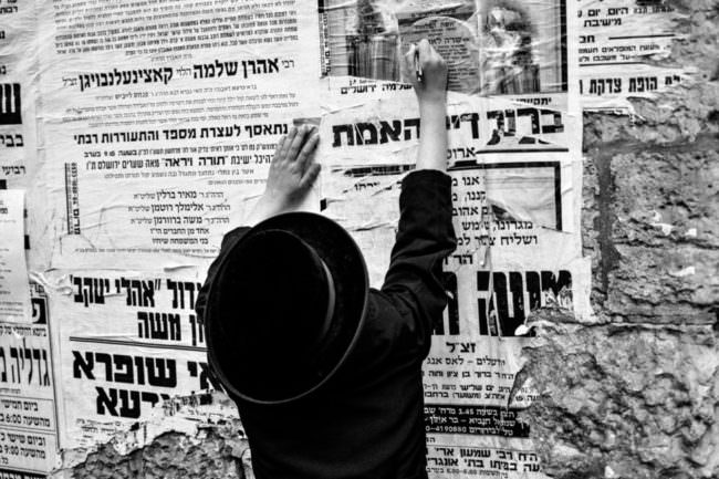 Ein in dunkle Kleidung gehüllter Mensch vor einer Mauer voller weißer Plakate in hebräischer Schrift