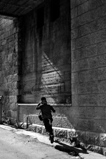 Ein Junge läuft eine Gasse entlang