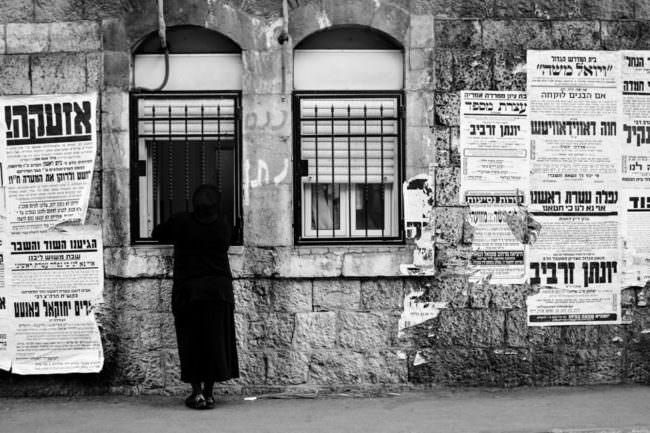 Eine Frau in einem dunklen schwarzen Kleid steht an einem Fenster