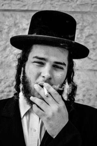 Portrait eines jungen Mannes mit Schläfenlocken, Hut und Zigarette