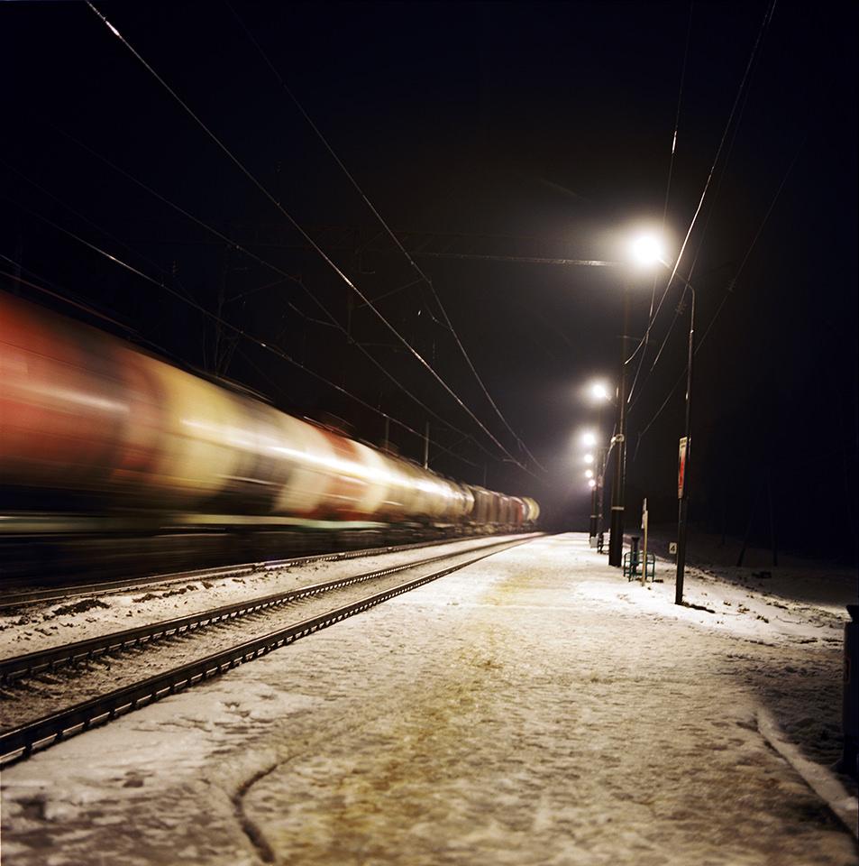 Ein Zug rauscht an einem dunklen Winterabend an einem schneebedeckten Bahnhof vorbei