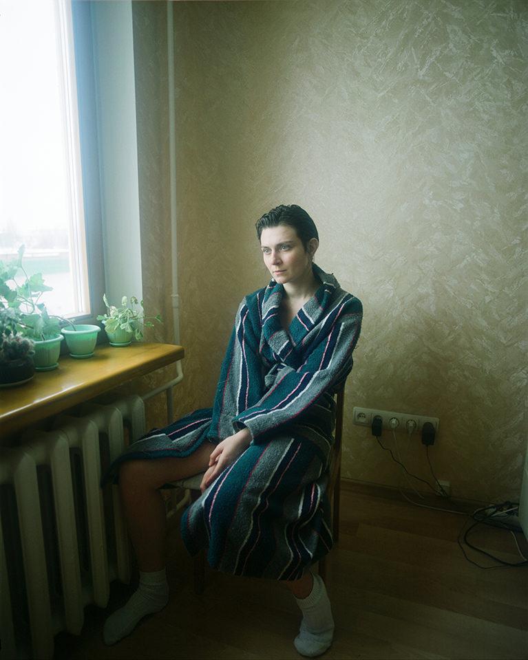 Eine Frau in einem Bademantel schaut aus dem Fenster