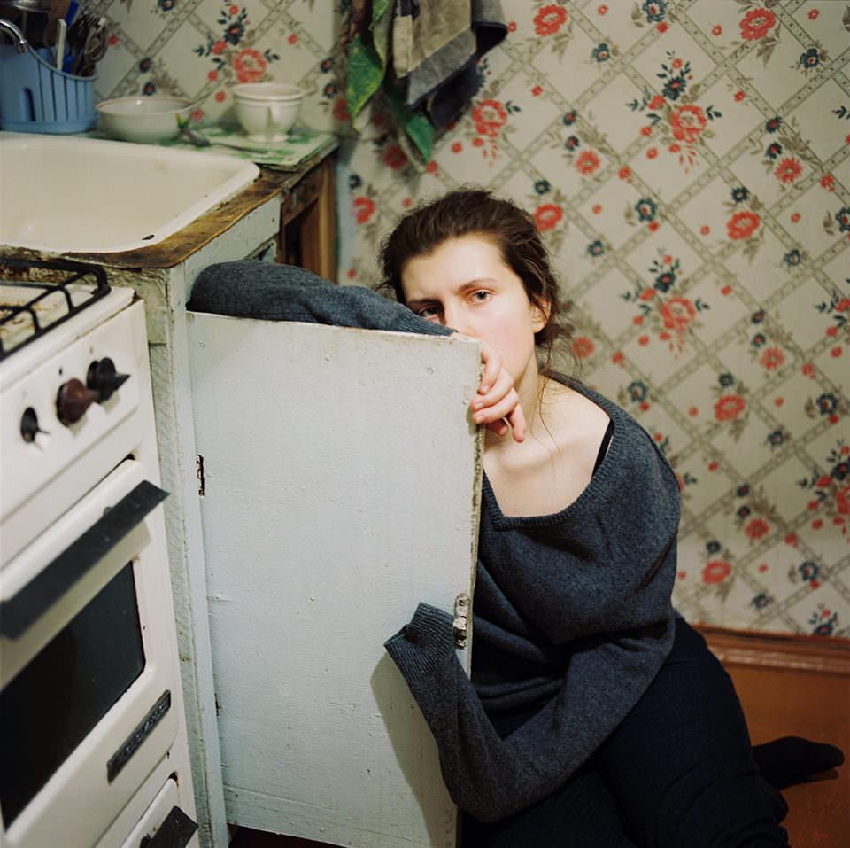 Eine auf dem Küchenboden sitzende Frau verbirgt ihr Gesicht hinter einer Schranktür