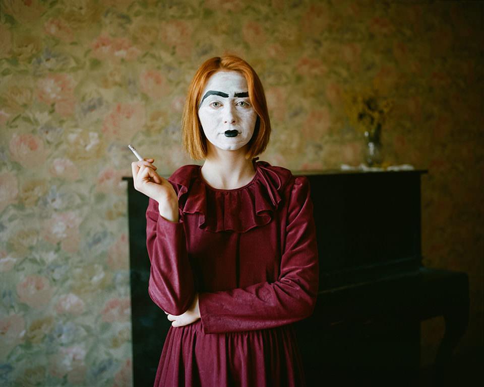 Eine Frau in einem roten Kleid mit einem Harlekingesicht steht vor einem Klavier und raucht