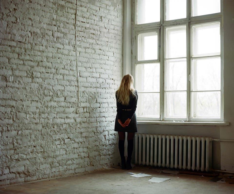 Eine blonde Frau steht in einem leeren Raum und schaut aus dem Fenster