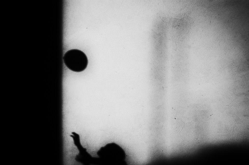 Ein Kind, ein Ball und Schatten.