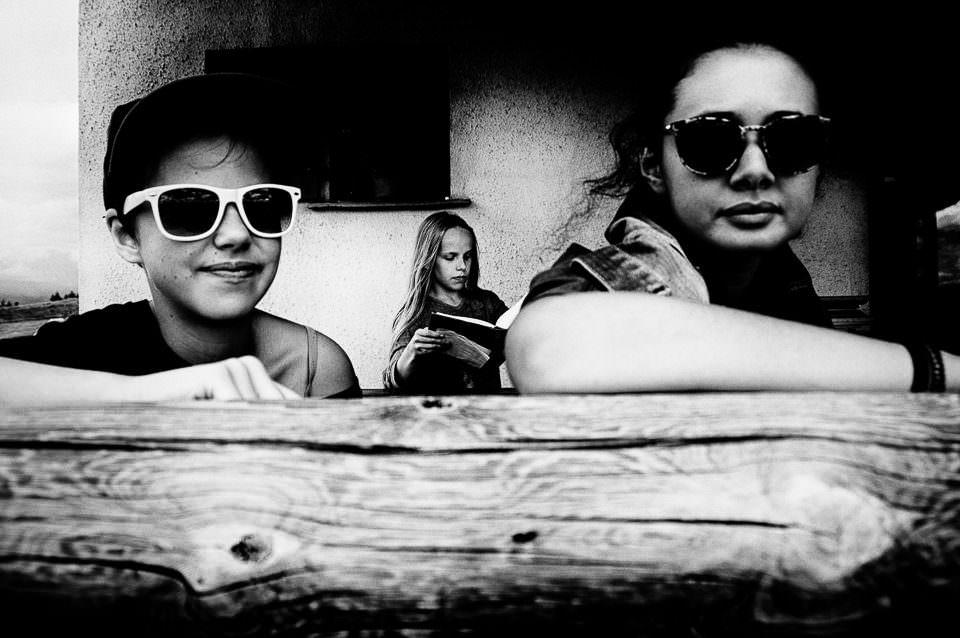 Zwei Kinder mit Sonnenbrillen und eines mit einem Buch.