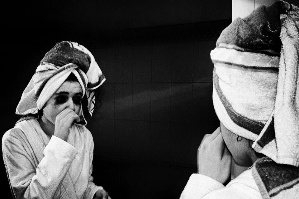 Ein Mädchen mit Turban und Bademantel und verheulten Augen.