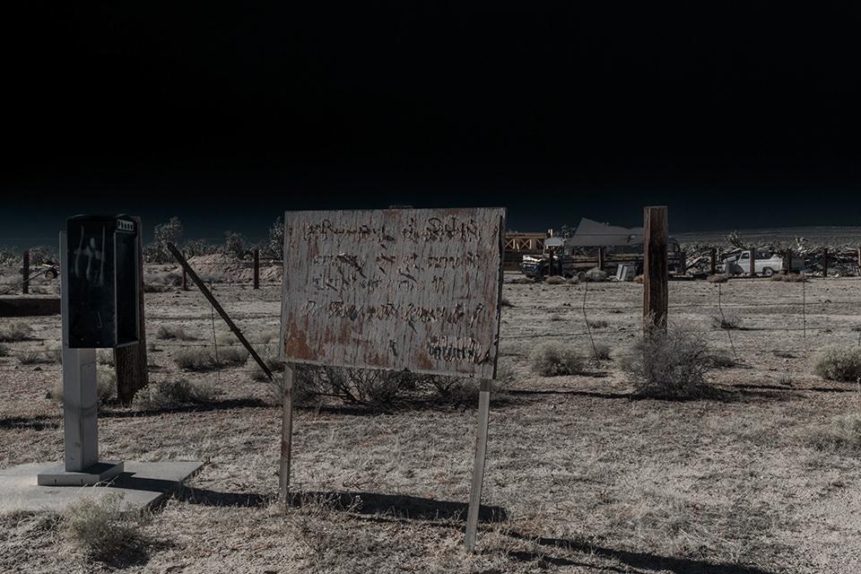 Eine ausgeleuchtete Wüstenlandschaft mit einem alten Schild und Stacheldrahtzaun.