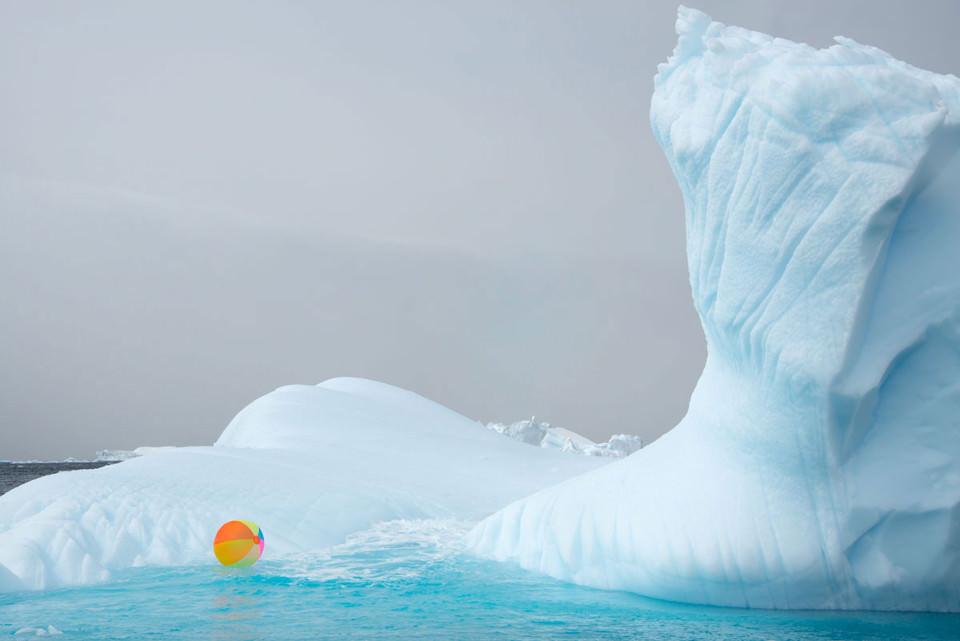 Ein bunter Wasserball schwimmt vor einem Gletscher.