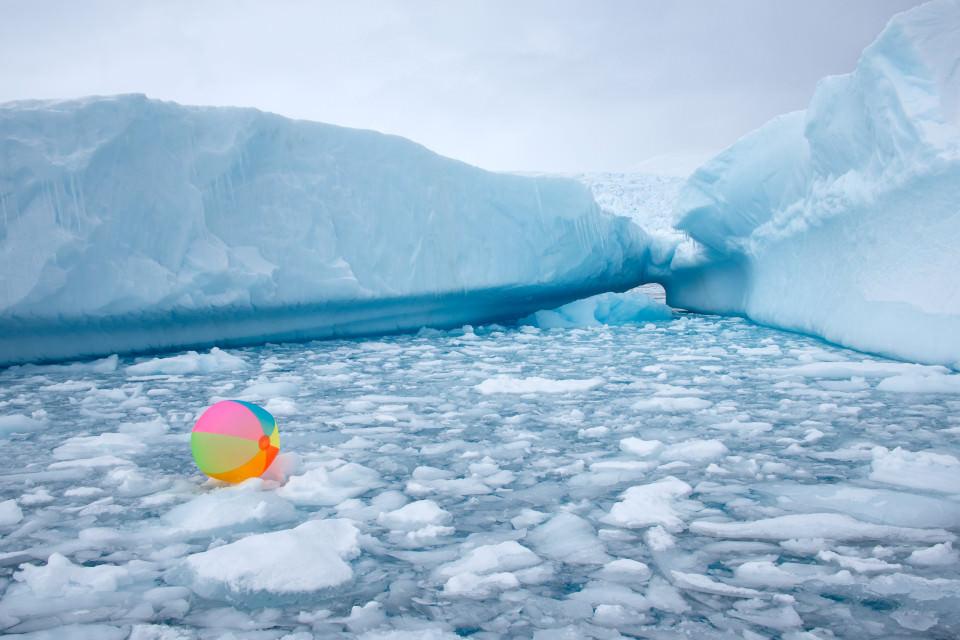 Ein bunter Wasserball schwimmt zwischen kleinen Eisschollen umher.