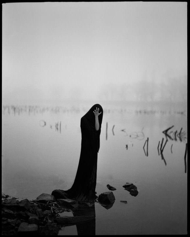 Eine in ein dunkles Gewand gehüllte Gestalt steht an einem Flussufer