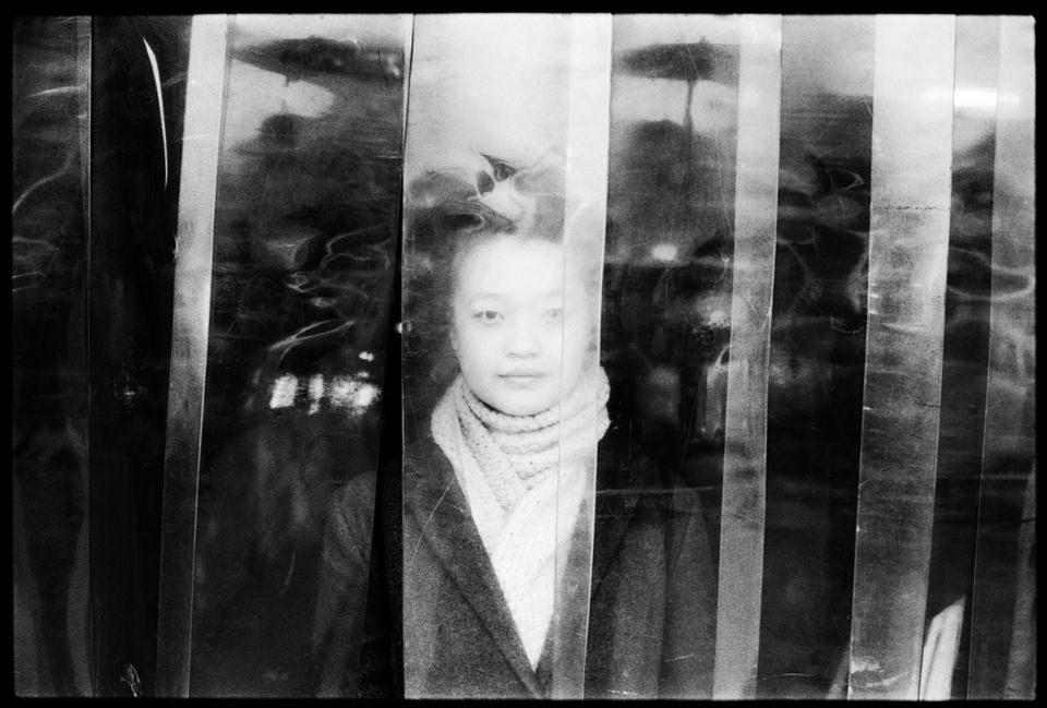 Eine Frau hinter einem Plastikvorhang